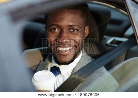 Portrait of confident African -American businessman riding in backseat of car smiling cheerfully looking at camera out of window lit by sunlight, holding coffee cup