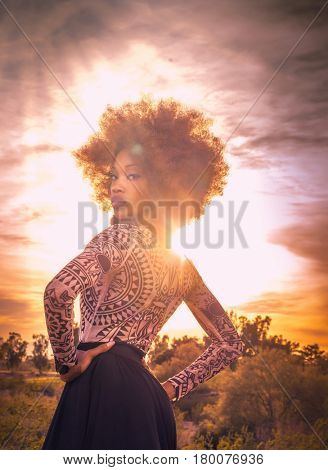 Beautiful  tall majestic woman posing dramatically as the sun sets behind her