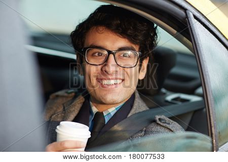 Portrait of enthusiastic Middle-Eastern businessman riding in backseat of car smiling confidently looking out of window lit by sunlight, holding coffee cup