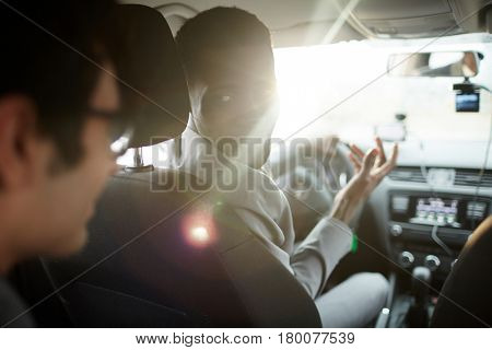 Portrait of African-American businessman driving car, turning to talk to passenger in backseat