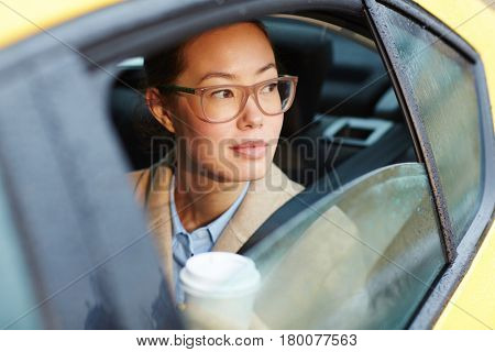 Portrait of confident Asian businesswoman riding in backseat of car  looking out of window lit by sunlight, holding coffee cup