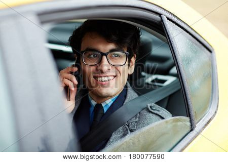 Portrait of smiling Middle-Eastern businessman riding in backseat of car speaking on phone and  looking out of window