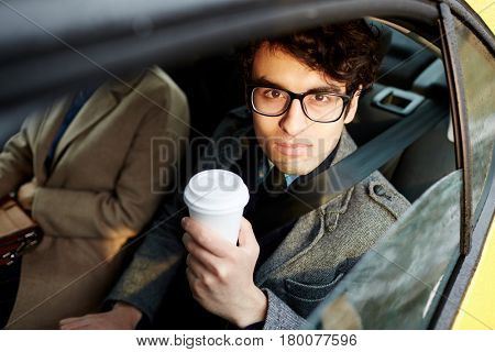Portrait of confident Middle-Eastern businessman riding in backseat of car smiling cheerfully looking at camera out of window lit by sunlight, holding coffee cup