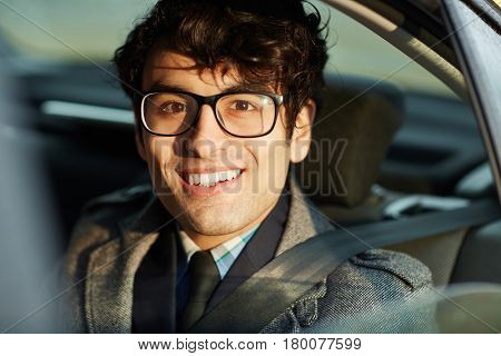 Portrait of enthusiastic Middle-Eastern businessman riding in backseat of car smiling confidently looking at camera lit by sunlight
