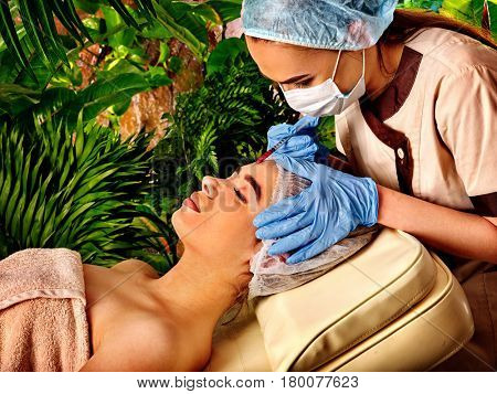 Filler injection for female face. Plastic aesthetic facial surgery by doctor in beauty clinic. Beauty woman giving injections. Waterfall and green plants in background.