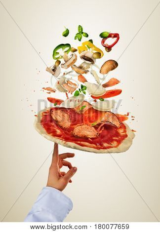 Chef hand preparing pizza dough with flying ingredients. Isolated on bright background. Food preparation, fresh meal ready for cooking