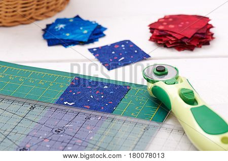 Quilting tools piece of fabric prepared to cutting two heaps cut off of fabrics