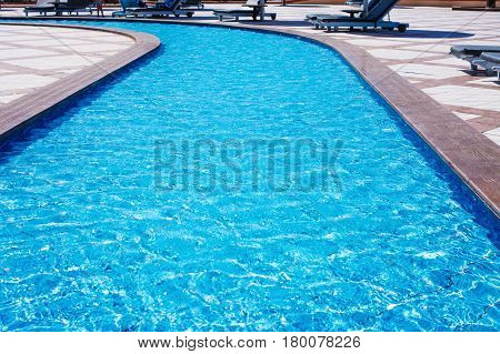 Pool with clean clear-water with sun loungers around it