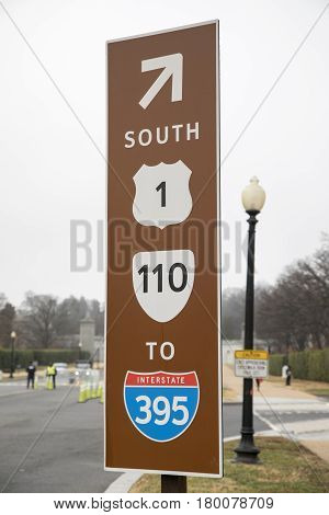A brown road sign for route 1, 110 and Interstate 395 in Virginia