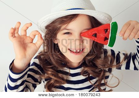 Little girl with big smile is showing OK by her fingers and covering her eye with a lollipop watermelon shaped. Image is on a white studio background. Good mood concept