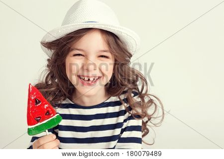 Girl with curly hair is smiling from ear to ear and holding a lollipop watermelon shaped. Picture is taken a studio and has white background. Childhood concept