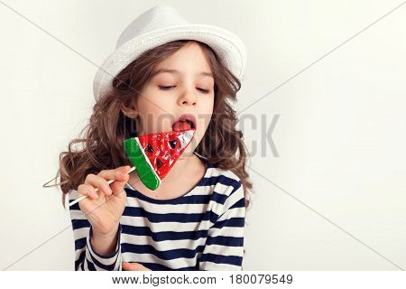 Young girl wearing white hat is licking a huge lollipop watermelon shaped with a pleasure and concentration at the same time.