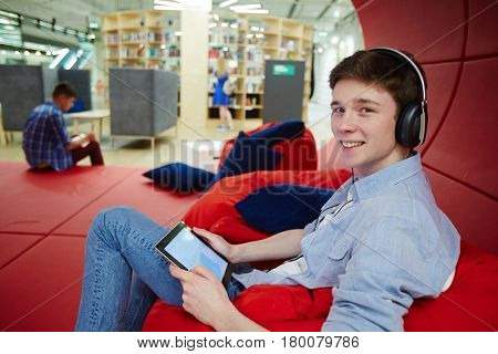 Portrait of smiling young man working in creative office workspace, relaxing on bean bags while using digital tablet and headphones