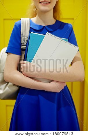 Midsection shot of smiling teenage girl holding books, dressed in blue dress against yellow background