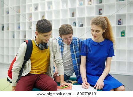 Portrait of three students working at group project together, pretty girl helping two boys with studying, explaining tasks in modern workspace