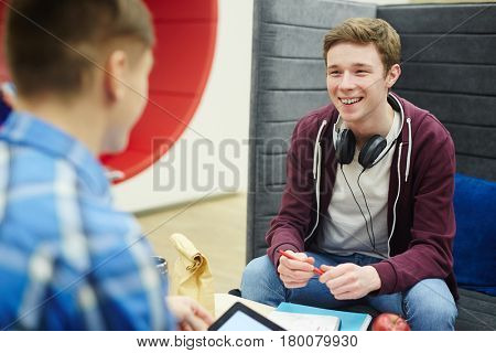 Portrait of smiling teenage boy talking to friend while sitting at table with books and lunch in college