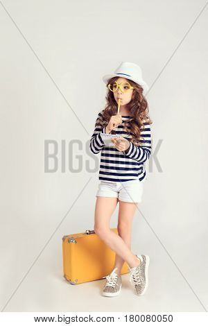 Serious young girl is standing by her yellow suitcase, holding notebook and pen and thinking about something. The picture is taken at studio and has white background