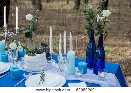 Wedding banquet table decorated with white wedding rustic cake with blueberry and greenery. Table served with cutlery, stemware and candles on a blue tablecloth