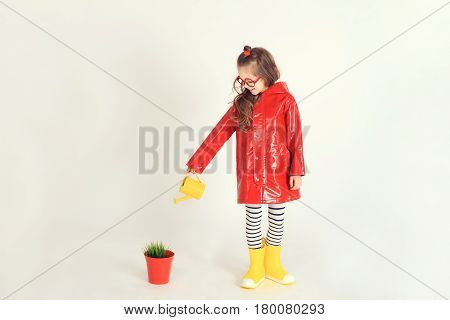 Young girl wearing raincoat and rubber boots is watering grass from a pot by using watering can. The picture is taken at studio and has white background