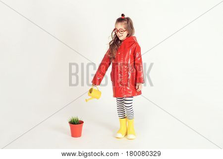 Smiling girl wearing raincoat and rubber boots is watering grass from a pot by using watering can. The picture is taken at studio and has white background