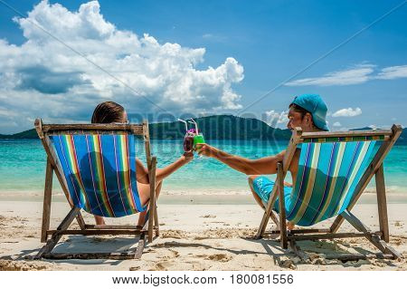 Couple in loungers clinking their glasses on a tropical beach at Thailand