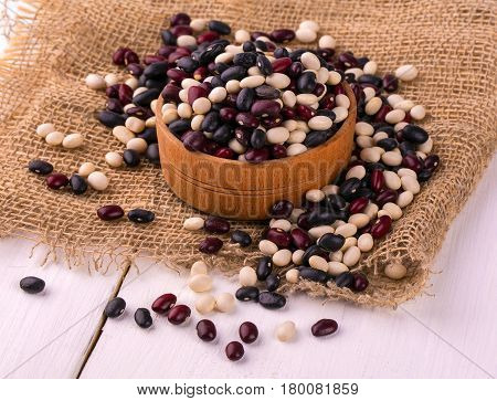 Colored haricot beans in a wooden cup and burlap on the white table