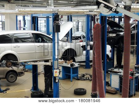 White vehicle on lift in small car service station stock photo