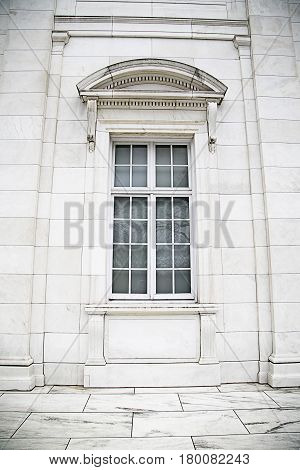 A window set in a white stone and marble building