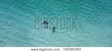 Aerial view of sup boards and swiming people on the sea. Top view beautiful water ripplles on a sunny day. View from above.