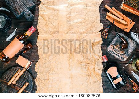 Frame of smoking pipes, cigars, tobacco and brandy bottles on dark wood desk and old paper. Western style. Top view