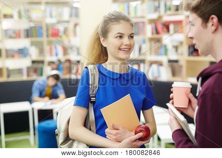 Portrait of pretty teenage girl talking to friend in college library, smiling and discussing schoolwork