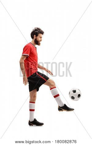 Full length profile shot of a bearded guy in a red jersey juggling a football isolated on white background