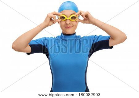 Female swimmer adjusting her swimming goggles isolated on white background