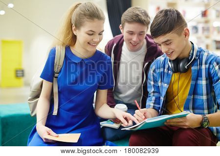 Group of smiling students discussing homework in college hall, boy writing with girl helping him