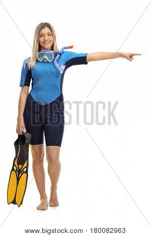 Full length portrait of a woman in a wetsuit with snorkeling equipment pointing right isolated on white background