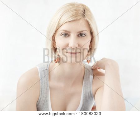 Closeup portrait of young blonde woman smiling, looking at camera.
