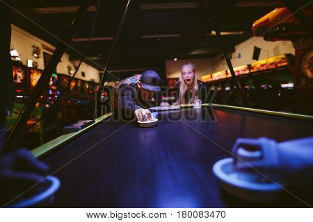 Happy Young Friends Playing Air Hockey At Amusement Park