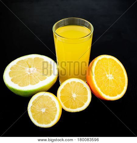 Natural juice of lemon, orange, mandarin, and sweetie on black background. Flat lay, top view. Fruit background