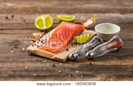 Salmon fillet sitting on table with cut lemon and some spices, ready to be cooked