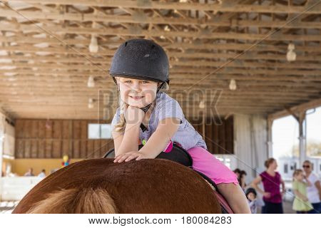 Lovely little girl sitting on a horse. Horse and jockey small - cute little girl in pink pants with a helmet and her best friend