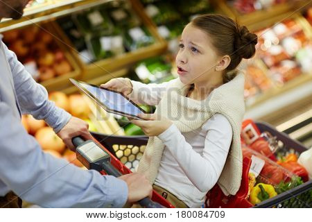 Dissatisfied girl with touchpad talking to her father in supermarket