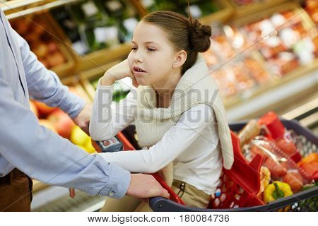Bored child sitting in shopping-cart while visiting supermarket with her father