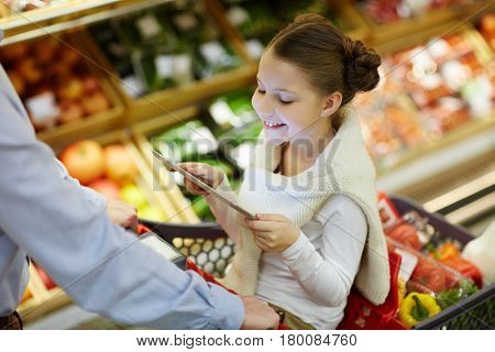 Little girl with touchpad sitting in shopping-cart