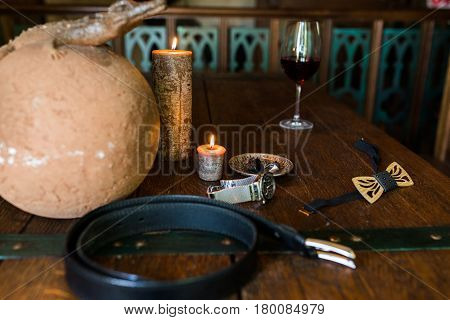 Men's rings in bronze plate on a wooden table and burning candle. Men's accessories. Wooden necktie.  Leather belt