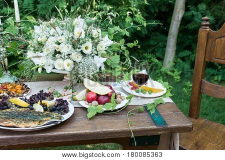 Served table for dinner with red nectarines, red berries, melon, nuts, grilled fish and a glass of red wine