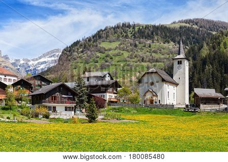 Beautiful Alpine landscape  with church  and typical Swiss houses  at spring sunny day , Inden village , canton of Valais , Switzerland.