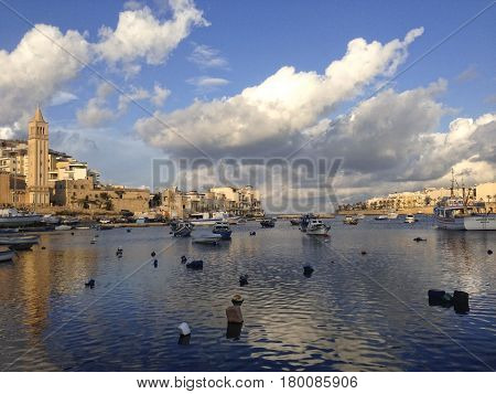 Marsaskala, MALTA-March 30: traditional Maltese fishing boats with reflection in the sea with nice clouds on beautiful sunset in maltese village Marsaskala, MALTA in March 30,2016
