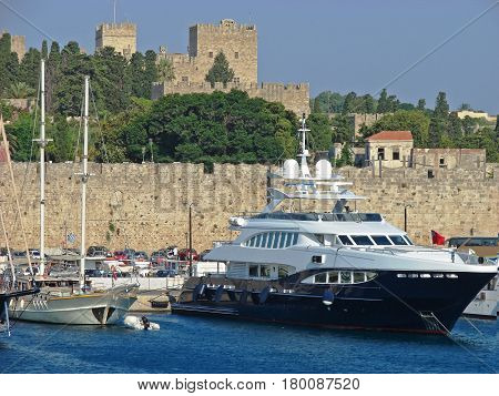 A view to the Rodos harbor with yachts and a stronghold on the hill
