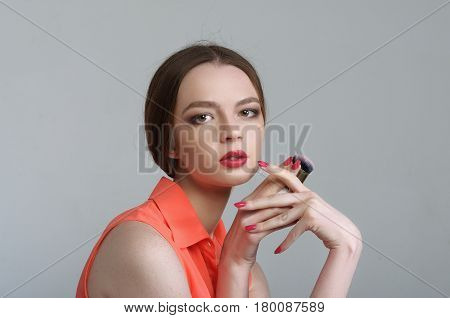 Girl Is Holding A Brush For Blush In Her Hand In Front Of Her Face