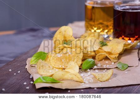 Potato chips with salt and greens on a table in a pub on a background of beer. Chips with greens as a snack to beer. October Beer Fest.